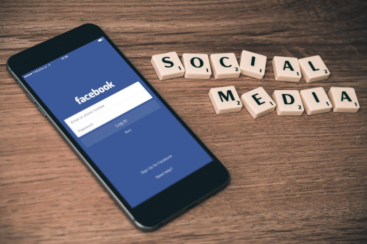 Handy mit Facebook App auf Holztisch, daneben Social Media Textbausteine